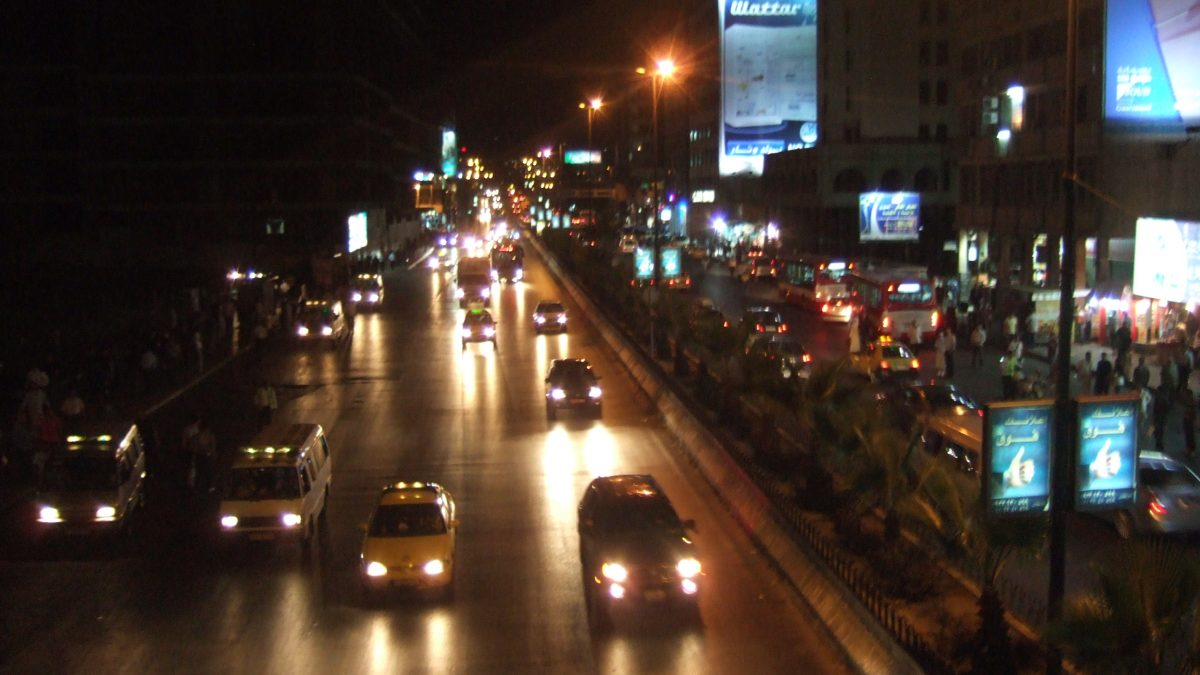 Cars driving down a busy road by night