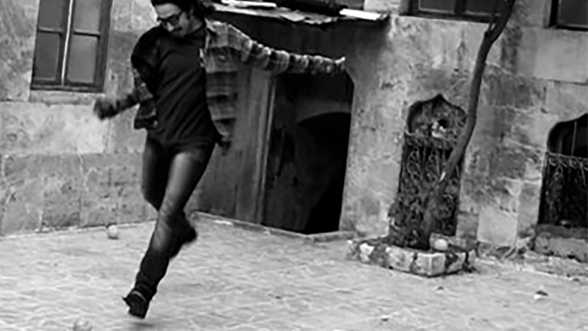 Man kicking an orange in a courtyard