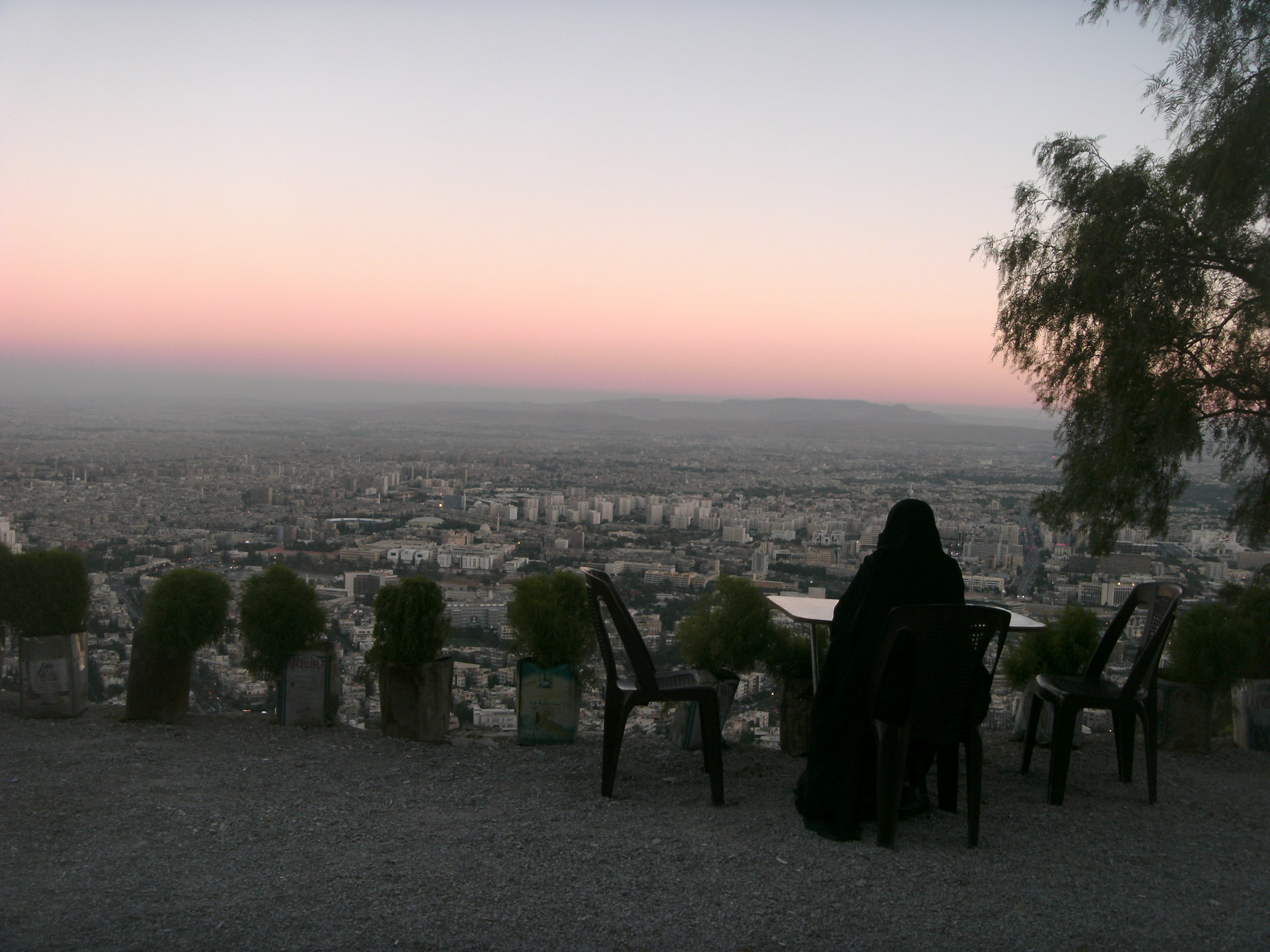 Woman looking over Damascus at sunset