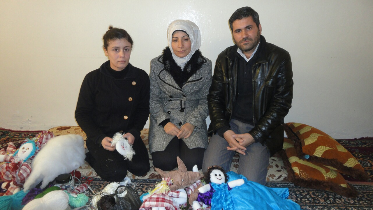 Hayat and family kneeling behind handmade toys
