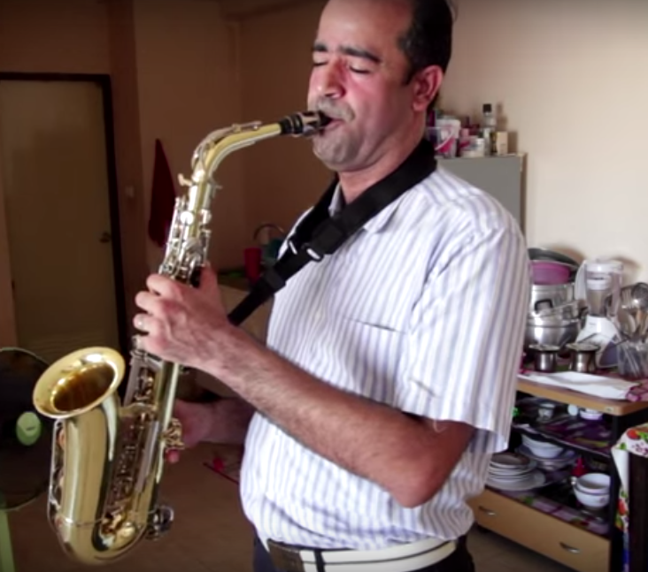 Man playing saxophone at home