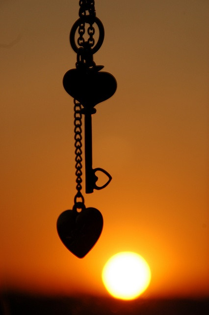 Heart and key silhouetted against sunset