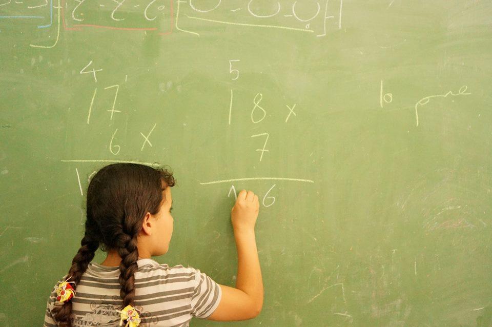 Girl writing sums on blackboard