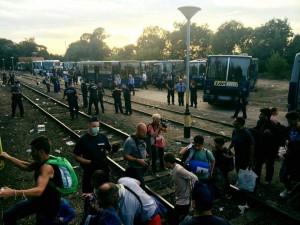Refugees walking over train tracks