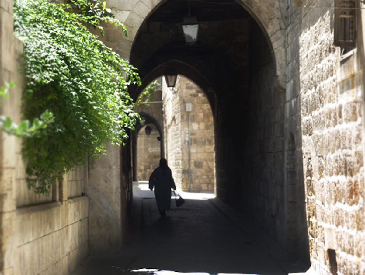 Person walks through an arch in an Aleppo street