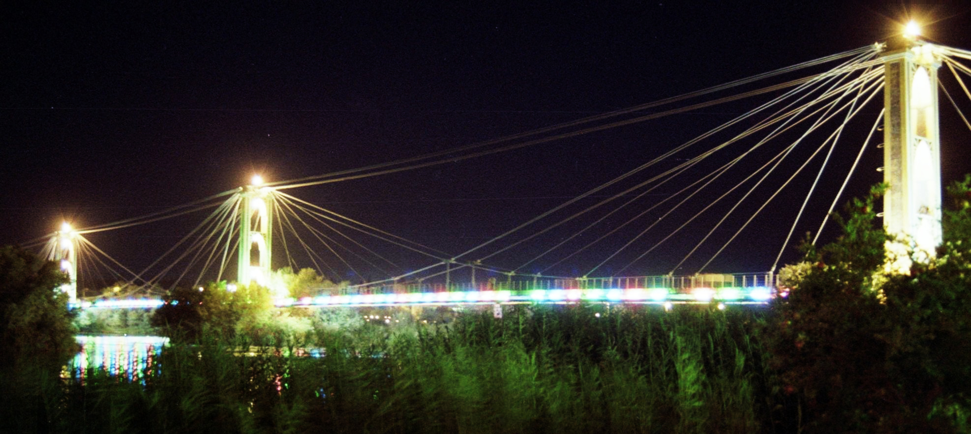 Deir ez-Zor suspension bridge at night in October 2010, by Fulvio Spada, used under CC BY-SA 2.0. / Contrast adjustment from original. The suspension bridge, which was built in the 1920s and spanned the Euphrates River, was destroyed in May 2013.